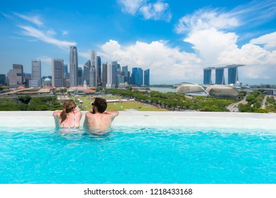 Couple business people relax in swimming pool on roof top behind beautiful city view Marina Bay Sand, the most famous tourist attraction in Singapore city, Singapore