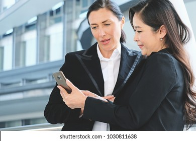 Couple of businesswomen looking and reading at smartphone screen and discuss about work, couple female pointing at something on laptop together, business people working on laptop and pointing screen