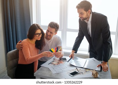 Couple buy or rent apartment together. They sit in front of realtor. Young woman look at colorful tissue pieces in hand and smile. Man embrace her and look at woman.