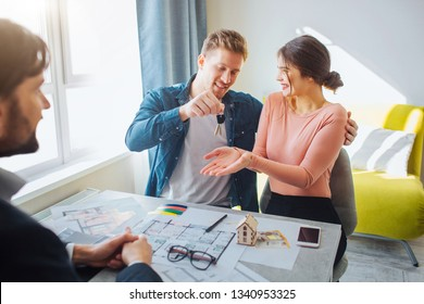 Couple buy or rent apartment together. Happy young woman get keys from man. Realtor sit in front of them. Apartment plan and phone on table.