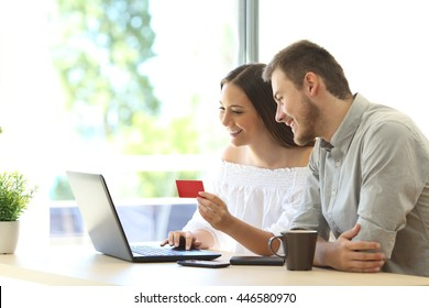 Couple of buyers buying on line with credit card and a laptop at home or hotel