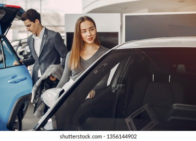 Couple buying the car. Pair in a car salon. Husband with vife choose the automobile