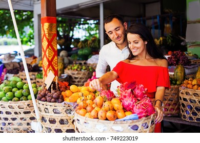 couple buying exotic fruits at traditional market in bali