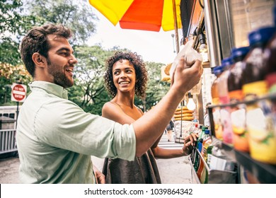 Couple buying a hot dog in a kiosk in New York