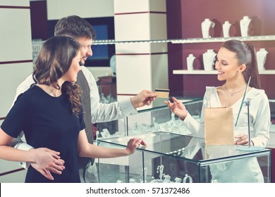 Couple buying jewelry in store and paying with card.