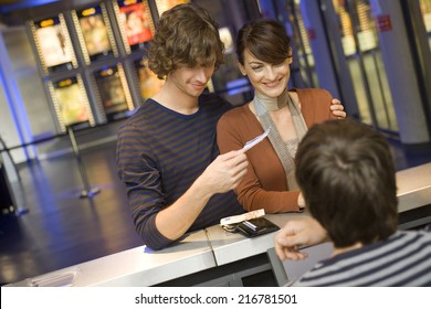 A couple buying movie tickets at the box office.