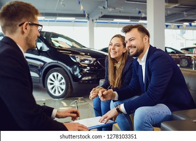 Couple buys a car in a car dealership