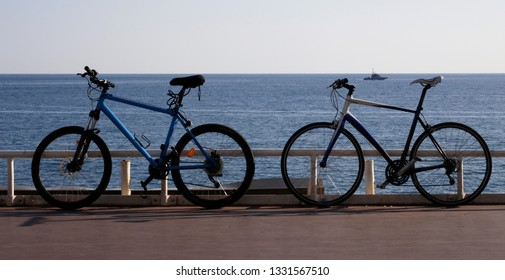 Couple of bycicles on embankment of sea / lake. Background photo on the subject of tourism, travel, transportation, sport, fitness, leisure, lifestyle. Conceptual image of love or friendship.