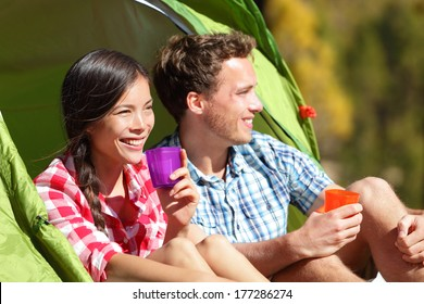 Couple camping drinking water in tent smiling happy outdoors in forest enjoying sun at looking at view. Happy multiracial couple relaxing after outdoor activity hiking. Asian woman, Caucasian man.