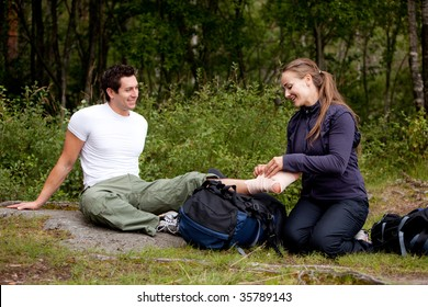 A couple camping and putting on a leg bandage