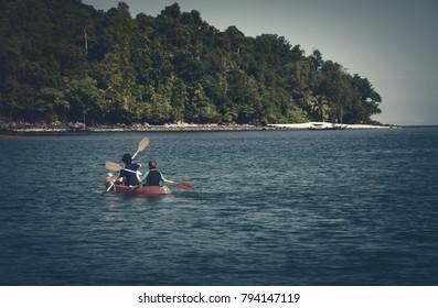 Couple canoeing or kayaking at sea island, Thailand.