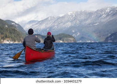 Couple canoeing on a wooden canoe in a beautiful Canadian Mountain Landscape during a vibrant winter day. Taken in Indian Arm, Vancouver, British Columbia, Canada.