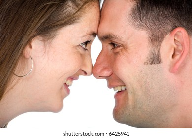 couple captured in a happy moment smiling and facing each other - isolated over a white background