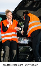 Couple with car breakdown wearing reflective vests calling towing company