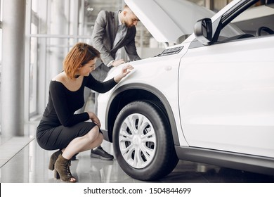 Couple in a car salon. Family buying the car. Elegant woman with her husband.