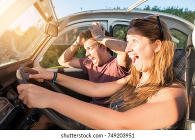 Couple in a car at sunset, with happy girl driving fast and boy scared, screaming and praying.