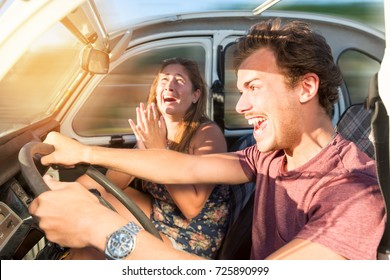 Couple in a car at sunset, with male driving fast and girl scared, screaming and praying.