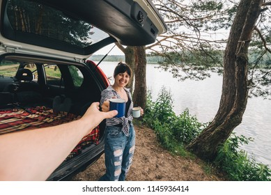 couple car travel. woman giving cup of coffee to man. first person point of view