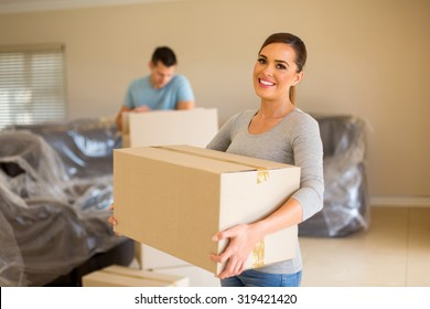 couple carrying boxes moving in new house