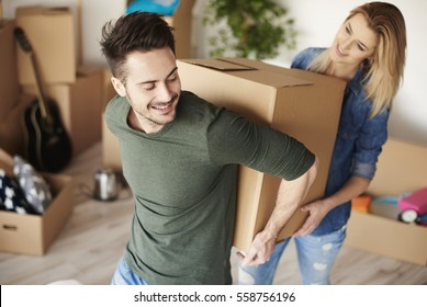 Couple carrying heavy moving boxes 260nw 558756196