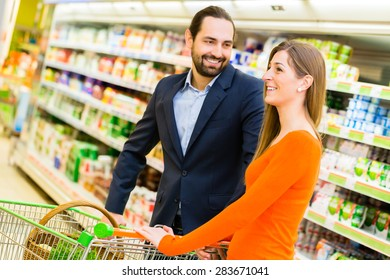 Couple with cart grocery shopping in supermarket