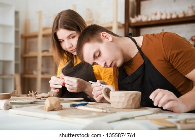 couple in casual clothes and aprons making ceramic pot on pottery at table in workshop