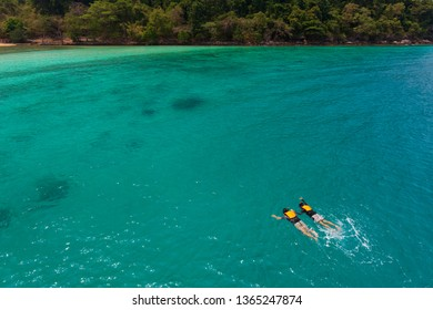 Couple catch each other hands and swim, skin diving to sea reef in clear water near island in Thai sea. Concept for sharing good time together and lifestyle of modern lovers