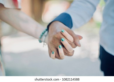 couple caucasian and african-american walking hand by hand outside. love, relationships, dating, sex