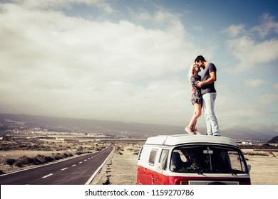 couple of caucasian man and woman people in love standing over the roof of a classic van vintage kissing and hugging. long way road on the side for travel and destination concept