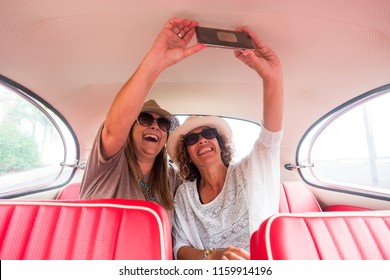 couple of caucasian middle age woman in outdoor leisure activity near and sitting on a red vintage car ready to travel.