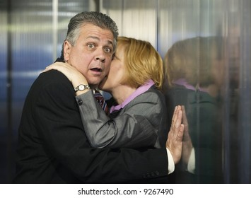 Couple caught in an embrace in a corporate office