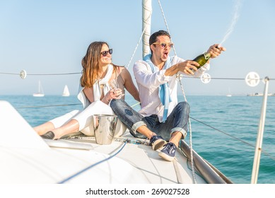 Couple celebrating with champagne on a boat .Attractive man uncorking champagne and having party with girlfriend on vacation.Two young tourists having fun on boat tour in the summertime