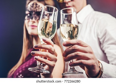 Couple celebrating New Year's eve drinking champagne on masquerade party