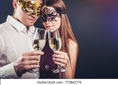 couple celebrating new years eve drinking champagne on masquerade party