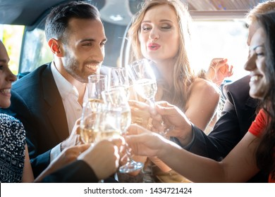 Couple celebrating party in limousine with friends and alcohol