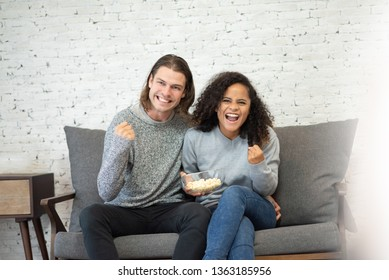 Couple celebrating and watching football game on TV at home together.