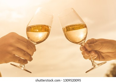 Couple celebrating with wine and a cheers at sunset.