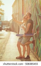 Couple with cellphone and skateboard enjoying in urban surroundings.