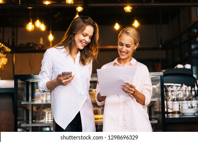 Couple of certain businesswomen are doing their team work in the cofee shop. Two successful colleagues are discussing their office plans in the cafe and looking at the reports they did yesterday.