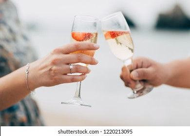 Couple with champagne glasses on the beach.