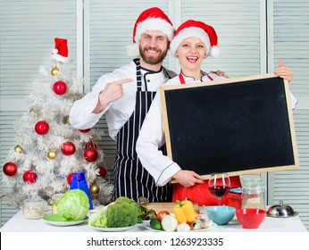Couple check list ingredients for christmas dinner. Christmas recipe concept. Menu for our family. Cooking christmas meal. Man and woman chef santa hat near christmas tree hold blackboard copy space.
