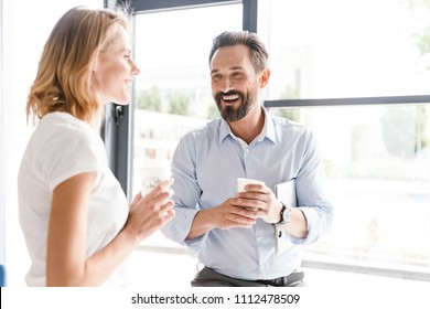 Couple of cheerful colleagues talking while standing at the office window with cups of coffee