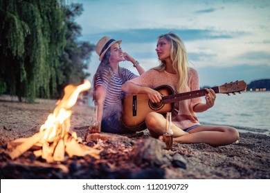 A couple of cheerful friends playing the guitar and having fun on the beach by the bonfire