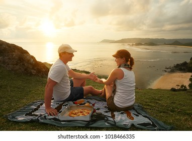 Couple of cheerful young people spending nice time together while sitting on the coastline and eating pizza