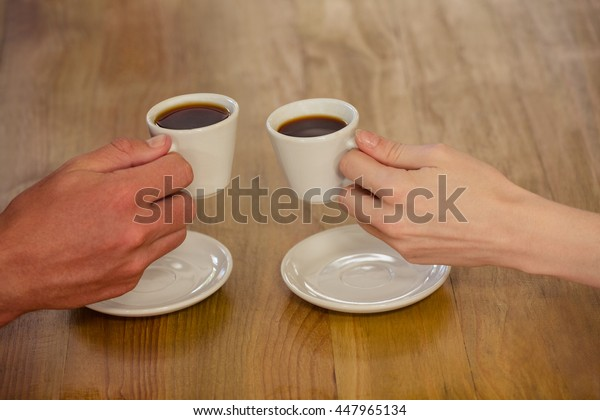 Couple cheering with espresso in the cafe