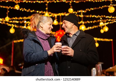 Couple cheering with mlled wine at Christmas market. Zagreb, Croatia.