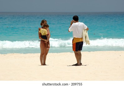 Couple with child in arms at the beach.