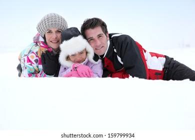 couple with child posing at ski resort
