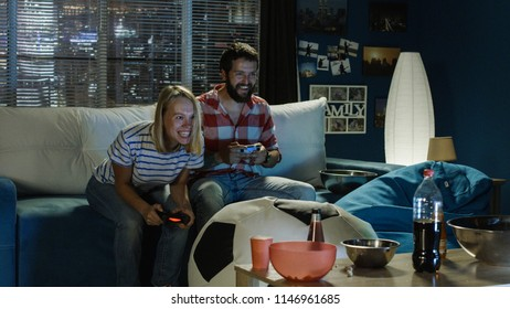Couple chilling on sofa with gamepad and man mocking on girlfriend when winning videogame round and having fun