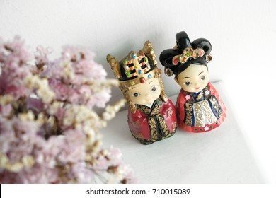 A couple of Chinese bride and groom doll with beautiful flower isolated on white wall background